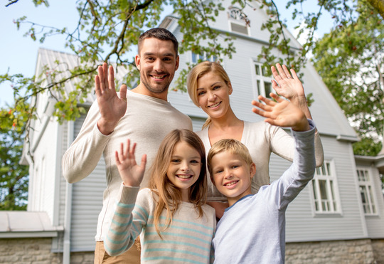 family in front of new home